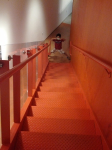 My son at the base of orange stairs with a dollar